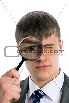 Young man looks through a magnifying glass