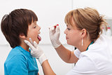 Health professional taking saliva sample from little boy