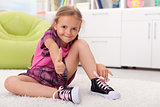 Little girl learning how to tie her shoes