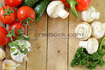 frame of vegetables (cucumber, tomato,mushrooms, garlic)  on a wooden background