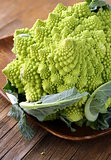 head of cabbage romanesco on wooden plate