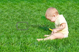 Pretty little boy sneezes sitting on a grass