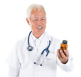 Asian senior doctor holding a bottle of pills