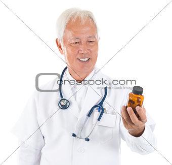 Asian senior doctor holding a bottle of pills
