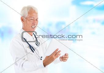 Asian senior doctor using tablet-pc
