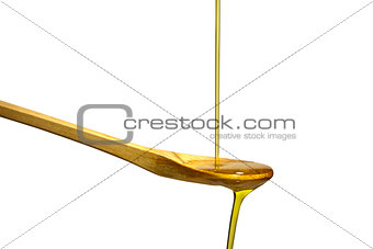Olive oil flowing over the wooden spoon