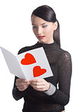 pretty brunette reads valentine postcard