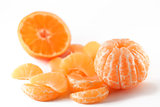 peeled mandarin and slices on white