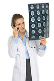 Medical doctor woman speaking cell phone and looking on MRI
