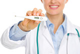 Closeup on thermometer in hands of smiling medical doctor