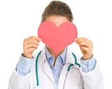 Medical doctor woman holding paper heart in front of face