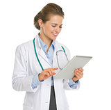 Happy medical doctor woman using tablet PC