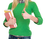 Closeup on student girl with books showing thumbs up
