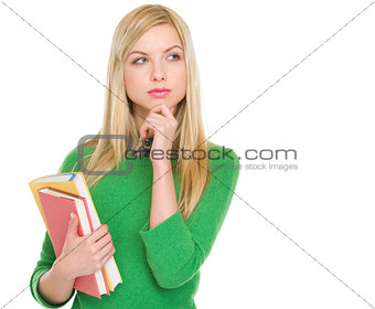 Thoughtful student girl with books looking on copy space