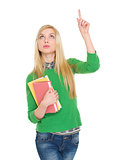 Happy student girl with books pointing up on copy space