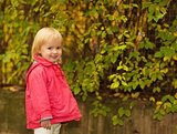 Portrait of baby in red coat outdoors
