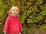 Portrait of happy baby in red coat outdoors