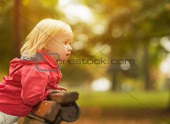 Baby leaning on bench and looking on copy space