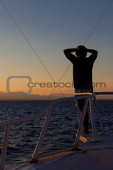 Person enjoying an ocean sunset