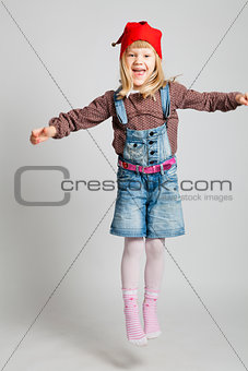 Smiling girl wearing Christmas hat and jumping