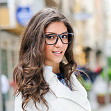 Beautiful woman with eye glasses smiling in urban background