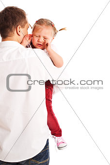 crying baby in the arms of his father