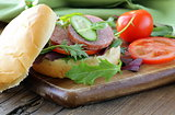 burger with salami and vegetables (cucumbers, tomatoes and lettuce)