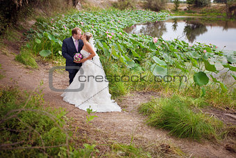 kissing bride and groom near lotos pond