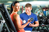 woman and Personal Trainer in gym with dumbbells