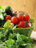 fresh vegetables (cucumbers, tomatoes, cabbage romanesco and green beans ) and herbs mix in a wicker basket