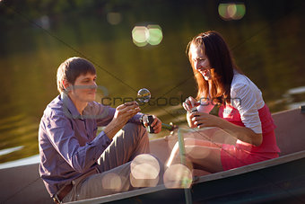 couple in a boat with bubble blowers