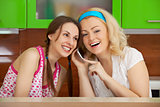 Two friends on kitchen get a phone call