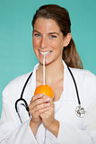 Attractive young female doctor sucking the juice from an orange