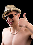Joyful young man in hat showing thumb up
