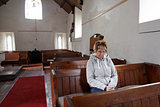 A woman sitting in an empty church praying