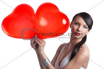 sexy brunette takes two heart shaped balloons with both hands