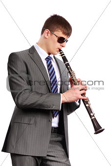Young musician with sunglasses playing the clarinet
