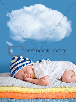 Little baby sleeping on stack of colorful towels with a dreaming