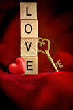 Gold key with wooden block letters that spell the word love