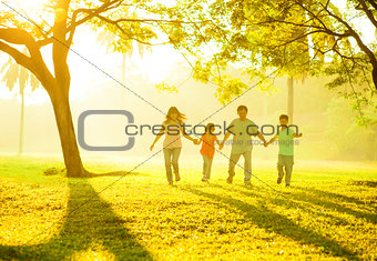 Asian family holding hands running