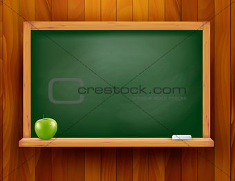 Blackboard with green apple on wooden background