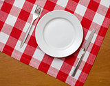 Knife, white plate and fork on wooden table with red checked tab