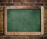 Aged green blackboard hanging on brick wall as a background for