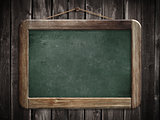 Aged green blackboard hanging on wooden wall as a background for