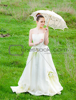 Beautiful bride with lace umbrella on green grass
