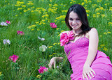 Young woman in pink dress sitting on green grass