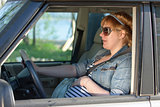 Pregnant woman speaking to her belly in the car