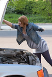 Pregnant Woman Opens the Hood of the Car