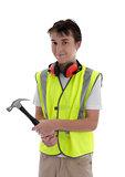 Young teen apprentice builder holding hammer