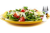 Salad with tomatoes, cheese and chicken in a yellow plate.